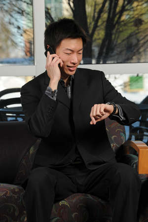 Portrait of young Asian businessman using cellphone while looking at watch