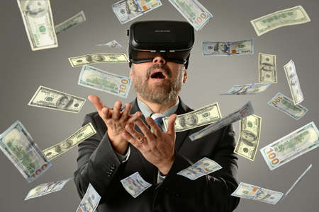 MAture businessman using virtual reality glasses getting money into hands Banque d'images