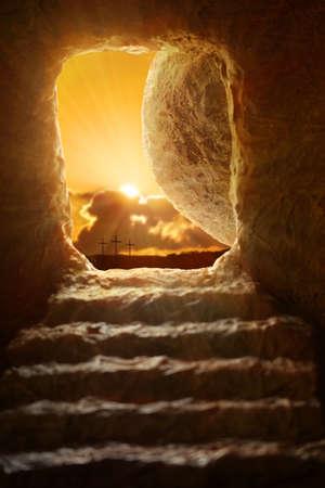 -石の上のフィールドの浅い深さの入り口から現れる太陽とイエスの開いている墓 写真素材