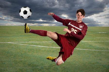 kicking ball: Young soccer player kicking ball while jumping