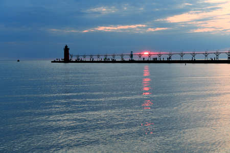 lake michigan lighthouse: Lighthouse and pier in South Haven Michigan at sunset