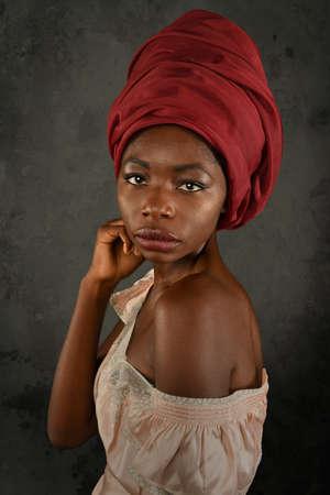 retrato: Joven mujer africana con turbante rojo sobre fondo gris