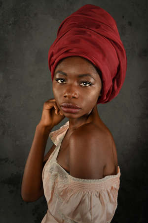 Young African woman with red turban over gray background