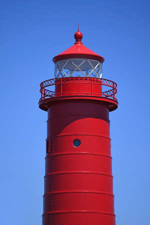 Red lighthouse over blue sky during daytime