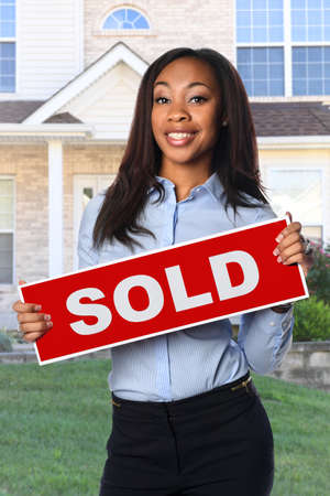 African American woman holding Sold sign in front of house