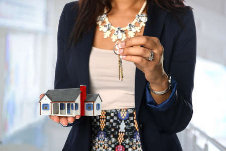Female real estate agent holding house and keys Banque d'images