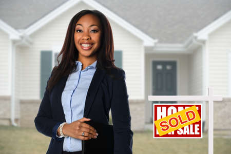 Mooie Afrikaanse Amerikaanse Real Estate agent inf voorzijde van huis verkocht Stockfoto