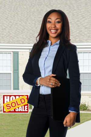 Young African American businesswoman smiling in front of sold home Banque d'images