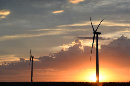 Wind turbines on flat land during sunset Banque d'images