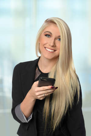 Beautiful businesswoman using cellphone inside office building