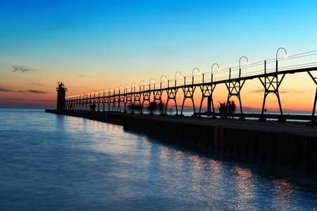 lake michigan lighthouse: Puesta del sol en el cielo del sur de Michigan con el faro y el muelle