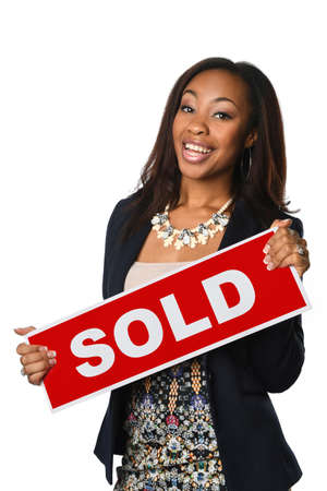 Portrait of beautiful African American businesswoman holding sold sign isolated over white background Banque d'images