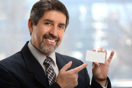 Portrait of senior Hispanic businessman pointing to blank business card inside office