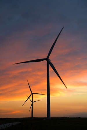 Wind turbines at sunset with motion blur on blades Banque d'images