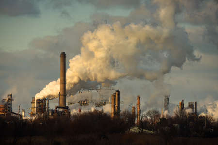 Heavy smoke being released from smokestacks in late afternoon Stock Photo