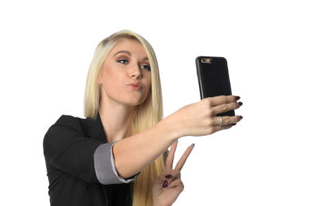 Young businesswoman taking selfie with cellphone isolated over white background Banque d'images