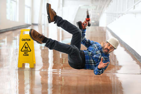Senior Hispanic worker falling on wet floor