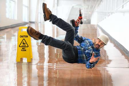 Trabajador hispano Senior cayendo sobre piso mojado Foto de archivo