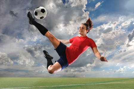 women playing soccer: Female soccer player kicking ball outdoors Stock Photo
