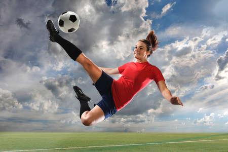 Female soccer player kicking ball outdoors Standard-Bild