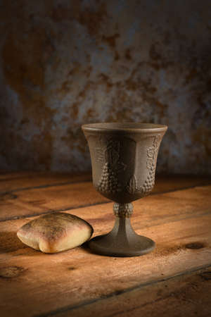 Bread and cup of wine on wooden table Stock Photo