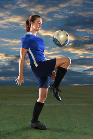 Female soccer player bouncing ball on knee at dusk Stockfoto