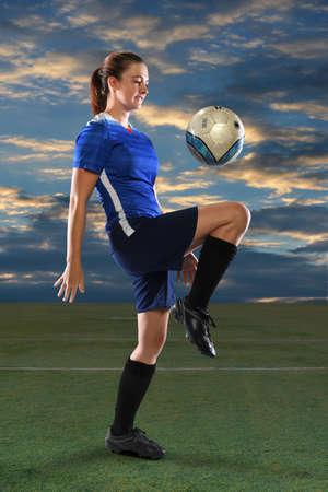 Female soccer player bouncing ball on knee at dusk Standard-Bild