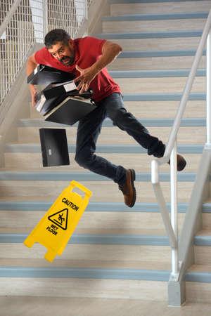 wet: trabajador hispano que lleva ficheros que caen en las escaleras mojadas