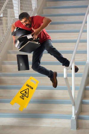 Hispanic worker carrying files falling on wet stairs Banque d'images
