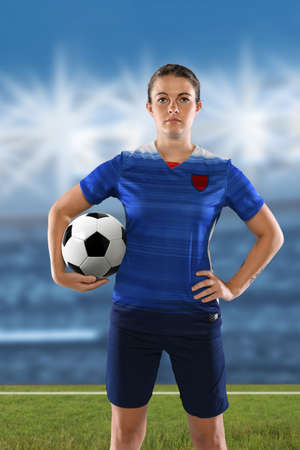 Portrait of female soccer player holding ball with stadium in background