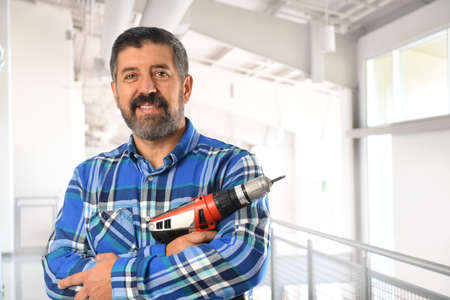 a drill: Hispanic man holding electrical drill inside building