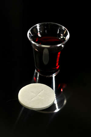 Communion wafer and cup with wine over dark background