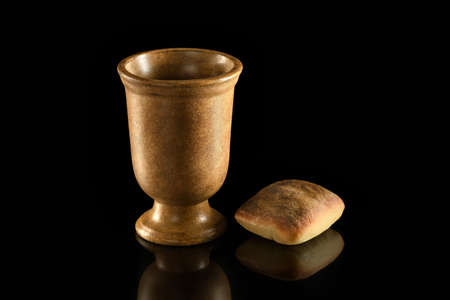 Cup of wine and bread on reflective table over dark background