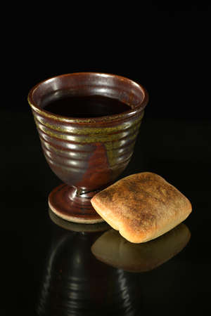 Cup of wine and bread on table over dark background Stock Photo