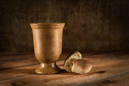 communion wafer: Wine goblet and bread as symbols of Communion on wooden table