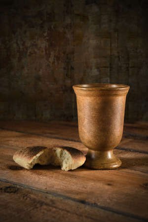 Communion wine cup and bread on wooden table Banque d'images