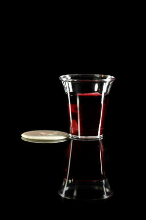 Communion cup with wine and wafer on reflective table over dark background