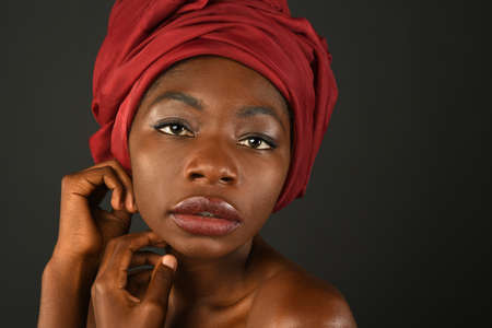 Portrait of African woman with red turban over dark background