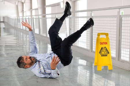 Hispanic businessman falling on wet floor inside office building Stockfoto