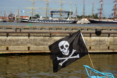 Black Pirate Flag flying form the top of a Mast on a boat in the port Stock Photo