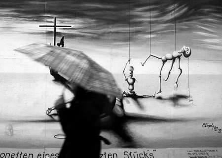 The Berlin Wall when it rains. A woman with a umbrella runs through the picture.