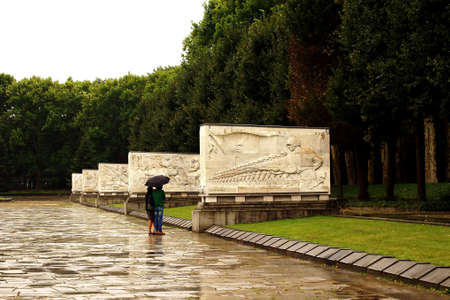 treptow: Two people are studying a relief of the Soviet memorial in Treptow in the rain.