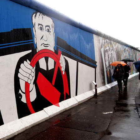 gorbachev: Berlin, Germany-January 02, 2012: The Berlin Wall (east side gallery) when it rains. A group of people passes a painted picture of Gorbachev.                 Editorial