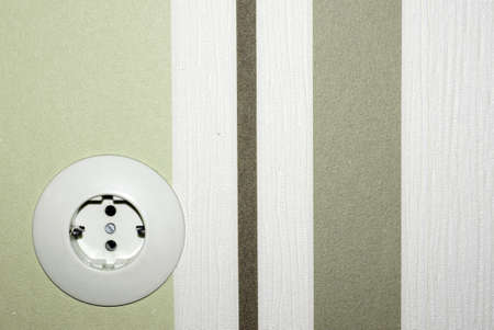 strikingly: The front view of an old outlet before a strikingly striped wallpaper                  Stock Photo