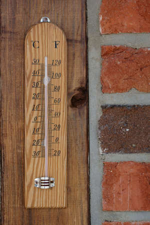 weather gauge: Close up of a thermometer on the outside of a brick wall