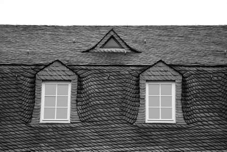 The photograph of a roof with scale-like arrangement of roof shingles