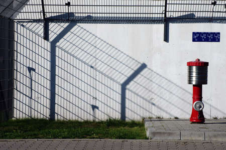 The architectural photography of a site perimeter fence, which casts a shadow and a fire hydrant                       photo