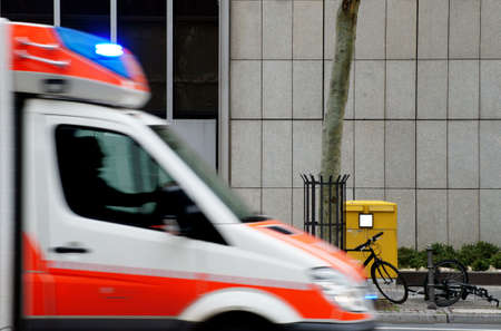 knocked over: The photograph of parked bicycles and a scooter in front of a mailbox where an ambulance passes with flashing lights                       Stock Photo