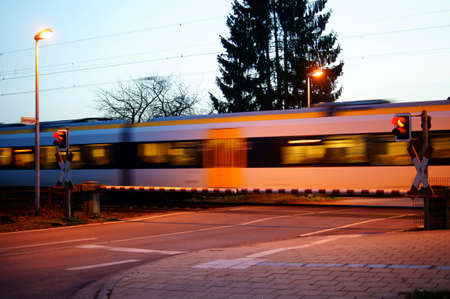 The photograph of a railroad crossing with a passing train in the evening                 photo