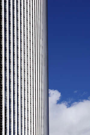 radiated: a high-rise building facade against the light with clouds and sky